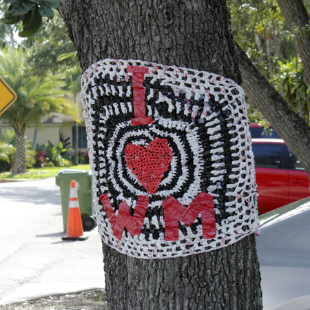 WILTON MANORS, FLORIDA - JUNE 23, 2013  A red white and black plastic and tape sign tied to a tree along Wilton Drive showing the letters I, a heart and initials WM, standing for I Love Wilton Manors