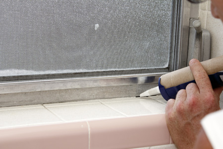 Caucasian male hand holding a blue caulking gun about to caulk a crack between an interior gray aluminum metal window frame and a speckled off white tile base of an old bathroom window sill in the day