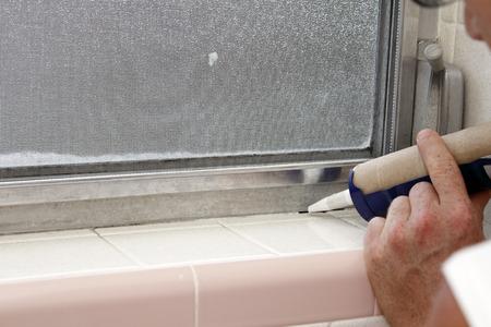내부 회색 알루미늄 금속 창 프레임과 일에있는 오래 된 화장실 창틀에 떨어져 얼룩덜룩 한 흰 타일베이스 사이의 균열을 코킹에 대한 파란색 코킹 총