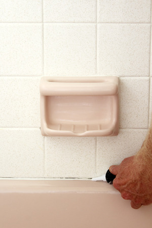 Caucasian hand of an adult man applying white mold resistant caulk to repair above the rim of a pink bath tub over an opened seam below speckled white tile wall of an old home to prevent water damage  Stock Photo