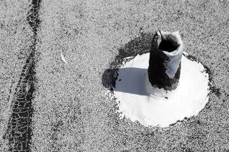 patched: Gray metal roof stack vent repaired so it is no longer leaking and black rubber is patched over with white rubber compound  Stock Photo