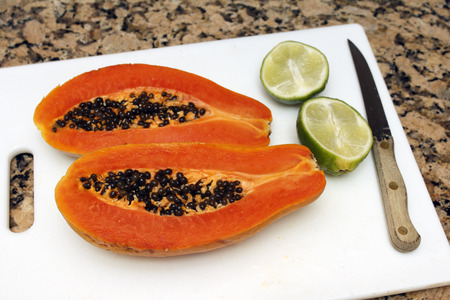 two and a half: One large dark orange papaya fruit cut in half lengthwise with black seeds inside next to two halves of a lime on a white cutting board near a knife on a brown and black granite kitchen counter top  Stock Photo