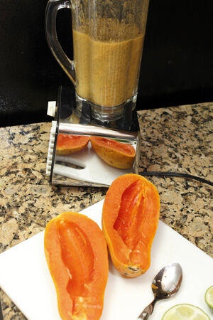 decades: Decades old chrome black white blender with blended papaya seeds in glass container and two halves of a long papaya on a cutting board with limes in front on a brown black kitchen granite countertop