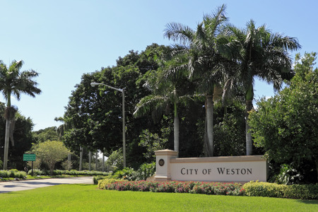 WESTON, FLORIDA - OCTOBER 22, 2013  Beautiful landscaping and flowers surround a large entrance sign to the City of Weston, located in west Broward County, population 67,641 in 2012 on a sunny day  Редакционное