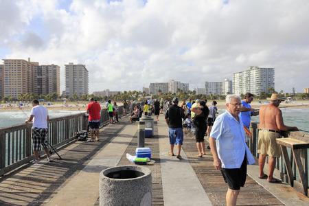 bathers: Pompano Beach, Florida - 22 dicembre 2013 Molte persone che pescano dalla lunghissima legno e cemento Pompano Beach Fishing Municipal Pier, con vista sulla spiaggia, bagnanti e gli edifici sulla costa