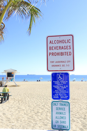 ordinances: FORT LAUDERDALE, FLORIDA - JANUARY 28, 2014: Signs at the beach park telling people to not bring alcoholic beverages inside, where handicap access is and that only trained service animals are allowed.