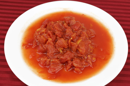 Twenty eight ounces of peeled and chopped red tomatoes with natural juice on a round white plate over a red striped table cloth background