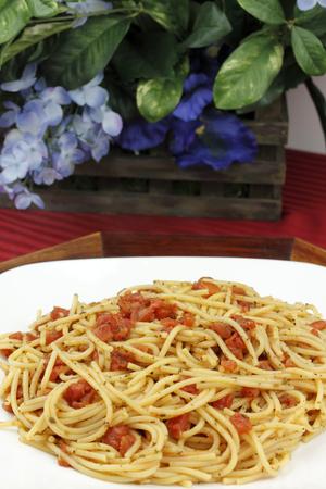 durum: Plaque blanche pleine de d�licieux spaghetti de bl� dur � d�s, les tomates et herbes biologiques fix�es sur un plateau en bois avec des fleurs bleues en arri�re-plan sur une nappe rouge