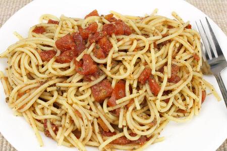 durum: Spaghettis de bl� dur cuites m�lang�es avec des tomates et des herbes coup�es sur un plat rond blanc plac� sur un napperon de tissu tan
