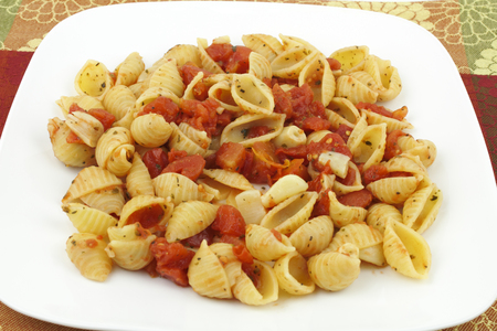 semolina pasta: Small conchigliette pasta shells prepared with diced tomatoes, many peeled garlic cloves, parsley, basil and oregano served on a white plate with a colorful background.