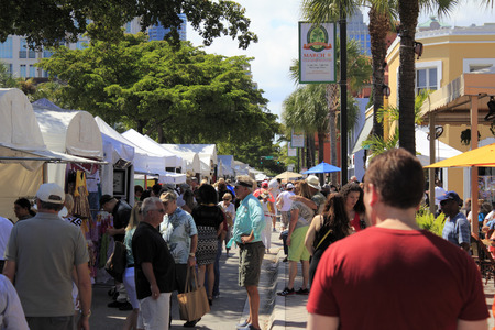 FORT LAUDERDALE, FLORIDA - MARCH 1, 2014  Crowds of people peruse and enjoy the large variety of art for sale at the weekend long Las Olas Boulevard art fair downtown on a sunny and tropical day