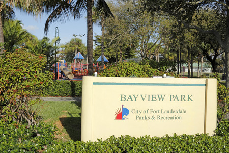 upscale: FORT LAUDERDALE, FLORIDA - FEBRUARY 23, 2014  Bayview Park sign, located on Bayview Drive in the upscale neighborhood of Coral Ridge Country Club Estates with playground equipment, trees and nature  Editorial