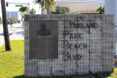 FORT LAUDERDALE, FLORIDA - FEBRUARY 14, 2014  Metal Oakland Park Beach Blvd Sign with dedication background information plaque and image of James S Hunt on a gray concrete wall
