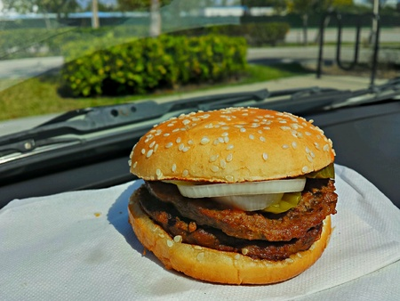 Fast food double hamburger with extra onions on a napkin in a sunny auto dashboard front window area Stock Photo - 28602339