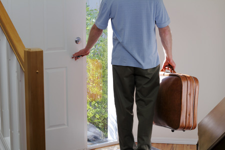 go inside: A man carrying a suitcase about to walk out the front door of his house to travel