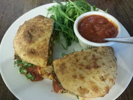 Free range organic chicken sandwich with marinara tomato sauce, arugula lettuce leaves