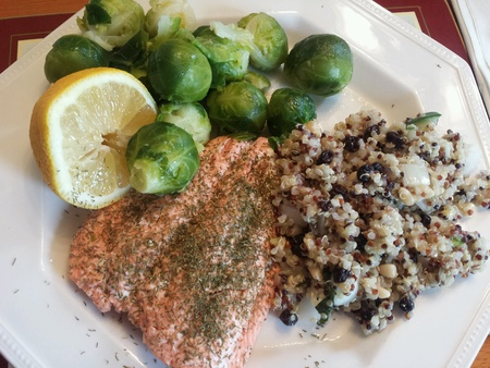 black currants: Wild salmon fillet with dill herb and lemon half, organic tri color quinoa salad with black currants