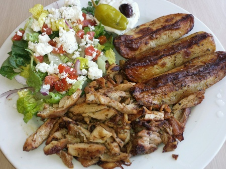 casual: Greek salad with shredded chicken and lemon potato wedges for a casual dinner Stock Photo