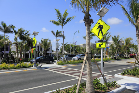 median: LAUDERDALE-BY-THE-SEA, FL, USA - APRIL 7, 2014: Four lane with median pedestrian crosswalk located in a refurbished area of tropical southern Florida, Lauderdale by the Sea. Palm trees and foliage line the median of this four lane street crosswalk across