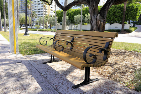 ft lauderdale: FORT LAUDERDALE, FL, USA - APRIL 7, 2014: A wood bench on a sunny day in front of tropical Galt Ocean Mile Drive with tall residential buildings trees and foliage. A partially shaded relaxing bench along a public urban community street with plants and nat Editorial