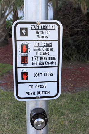 posted: FORT LAUDERDALE, FL, USA - APRIL 7, 2014: Close up of the instructions for crossing a crosswalk located on an urban street. The crosswalk instructions and warnings are posted on a silver metal light pole in front of foliage on a city street.