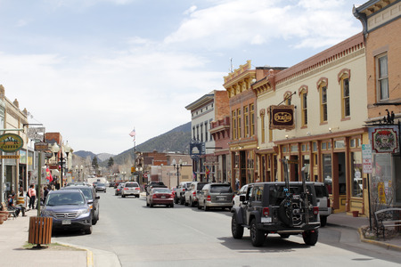 district: Idaho Springs, CO, USA - April 19, 2014: A sunny, commercial area of Miner Street where a lot of stores and shopping happens.Many people, vehicles and merchants line the downtown shopping area on the sunny street on a day in spring.