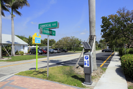 ave: LAUDERDALE-BY-THE-SEA, FL, USA - APRIL 7, 2014: Solar powered digital public parking meter and parking spaces north of intersection of Commercial Blvd and E Tradewinds Ave. About fourteen public parking spaces in the lot at the corner of E Tradewinds Ave