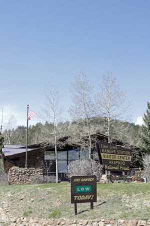 Idaho Springs, CO, USA - April 23, 2014: The Visitor Center and Clear Creek Ranger Station of the  Arapahoe National Forest. Vertical front view of a forest service building with trees, lawn and signs out front on a sunny day.