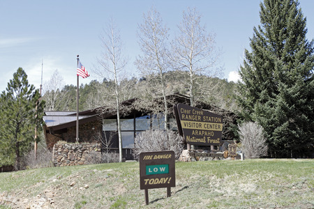 Idaho Springs, CO, USA - April 23, 2014: Clear Creek Ranger Station Visitor Center for the    Arapahoe National Forest. Front view of a forest service building with trees, lawn and signs out front on a sunny day. Editorial