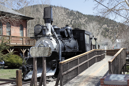 black train: Idaho Springs, CO, USA - April 23, 2014: Front and side view of an old black train with historical information on a wood sign. A wooden walkway travels the length of the historical train to get a better closeup view.