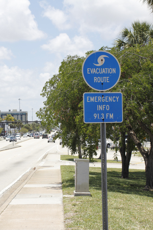 posted: FORT-LAUDERDALE, FL, USA - JUNE 5, 2014: Blue and white evacuation route and emergency info 91.3FM signs with a symbol of a wave on top posted along Oakland Park Boulevard on a sunny day.