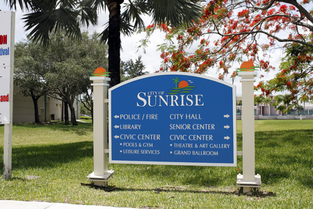 direction board: SUNRISE, FL, USA - JUNE 19, 2014: Large entrance sign that gives points with arrows to the various government agencies and building located in the area. Blue and white signage showing the way to different public buildings all located within a short distan