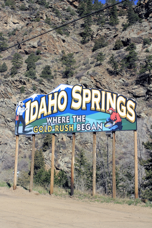 began: Idaho Springs, CO, USA - April 23, 2014: Colorful billboard sign on the North side of Interstate 70 just before town that says, Idaho Springs Where the Gold Rush Began. The large sign also shows a man with a mining pick and a man panning for gold in front