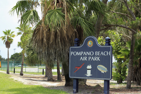 blimp: POMPANO BEACH, FL, USA - JUNE 21, 2014: Dark blue background sign that says Pompano Beach Air Park, along with City Of Pompano Beach, Florida. A red plane, a white tower and a Goodyear blimp also appear on the sign that is outside the green fence guarding