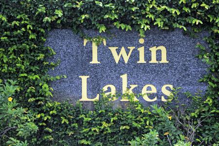 censo: Fort Lauderdale, FL, EE.UU. - 19 de junio, 2014: Twin Lakes barrio sur muestra de la entrada en grandes letras amarillas sobre un muro de piedra rodeada de escalada verde vid follaje con algunas peque�as flores amarillas. Twin Lakes en el condado de Broward es un CDP, o censo designado