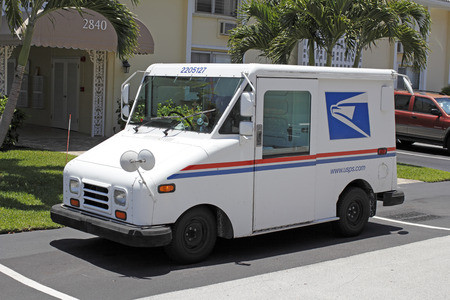 united states postal service: FORT-LAUDERDALE, FL, USA - JUNE 5, 2014: One white, blue and red United States Postal Service truck used to deliver mail parked in front of a residential condominium on a sunny day. USPS Mail delivery truck parked on a neighborhood street. Editorial
