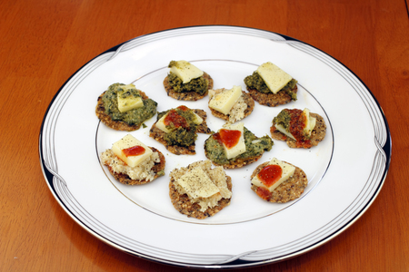 multi grain: Variety of round multi grain cracker appetizers topped with basil pesto or horseradish, cheese pieces, ground black pepper, and hot sauce on half of them. The round, white dish of snacks is on a wooden table top. Stock Photo
