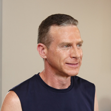 upper half: Half profile face and upper body of caucasian adult man in his forties looking off to the side dressed in a dark blue sleeveless sport shirt in front of a gray white wall.