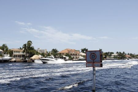 waterway: Pompano Beach, FL, USA - July 4, 2014: Boats travel in the intracoastal waterway creating good sized waves on this sunny day with a Manatee Zone 25 miles per hour sign closeup. Many boats seemed to be traveling quite fast this holiday weekend.