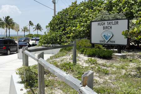 front entry: Fort Lauderdale, FL, USA - June 25, 2014: Beach front entry and sign to Hugh Taylor Birch State Park along A1A north of Sunrise Boulevard with beach, people, traffic on a sunny tropical day. Editorial