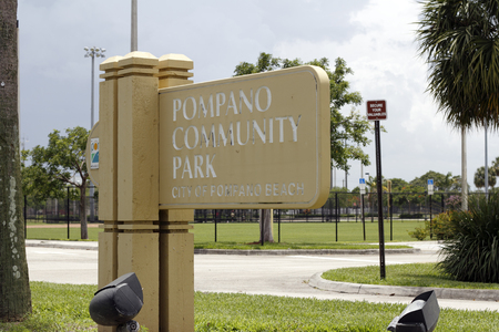 wood sign: Pompano Beach, FL, USA - June 21, 2014: Small painted wood sign post in front of areas of the park on a sunny day that says Pompano Community Park, City of Pompano Beach.