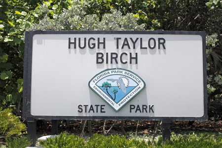 taylor: Fort Lauderdale, FL, USA - June 25, 2014: Large rectangle painted wooden Hugh Taylor Birch State Park sign located along  State Route A1A north of Sunrise Boulevard on a sunny day. The signage also says, Florida Park Service Environmental Protection.
