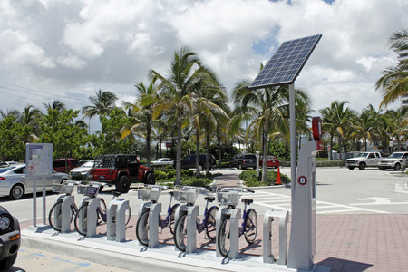accepts: Fort Lauderdale, FL, USA - July 24, 2014: Several bicycles for rent at an automated kiosk located at the beginning of the Fort Lauderdale Beach Park parking area. This kiosk, powered by a solar panel, accepts payments to rent the bicycles to people