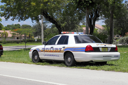 pulled over: Lauderhill, FL, USA - July 11, 2014: One Lauderhill, Florida police car pulled another car over and was stopped behind it along side a street in Lauderhill. A police cruiser was parked on the side of the road grass with its lights on during the day. Editorial