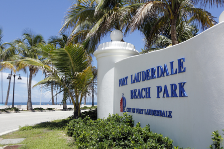 amenities: Fort Lauderdale, FL, USA - July 24, 2014: Wide view of Fort Lauderdale Beach Park in large white sign in front of the Atlantic Ocean. Landscape view of the main south beach in Fort Lauderdale with the most use and amenities.