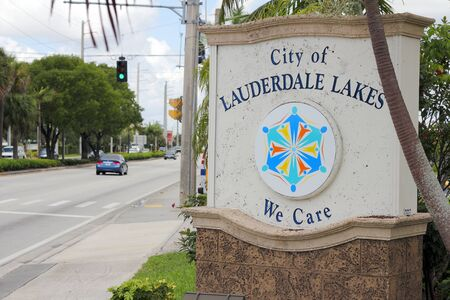 we the people: Lauderdale Lakes, FL, USA - July 11, 2014: City of Lauderdale Lakes Sign, We Care, entrance sign along the street during the day. There is an emblem on the sign of people radiating from their feet out from the center.
