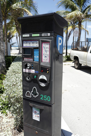 accepts: Fort Lauderdale, FL, USA - July 24, 2014: Large, electronic parking meter at Fort Lauderdale Beach Park on a sunny day with a view of the Atlantic Ocean. Digital parking meter at the beach that accepts several ways to pay.