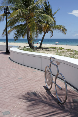 fort lauderdale: Fort Lauderdale, FL, USA - July 24, 2014: A gray metal bicycle rack in the form of a bicycle with a view of the Atlantic Ocean sunny beach beyond. One bicycle rack shaped bike at the beach that says, Green Your Routine, City of Fort Lauderdale. Editorial
