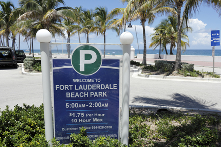 visitors area: Fort Lauderdale, FL, USA - July 24, 2014: Large sign in the public parking lot of Fort Lauderdale Beach Park that welcomes visitors to the area. The parking sign also lists the hours, cost, maximum parking time allowed, and a customer service number.