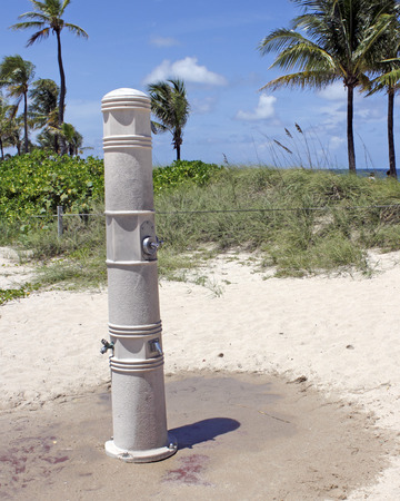showers: One tall cement column that has one shower near the top, two middle controls and two showers for the lower legs  on a sand covered red paver walkway near the dunes on a Fort Lauderdale, Florida beach. Stock Photo